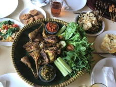 Centre: chef's recommendation, whole grilled chicken. Top, left to right: oseng keciwis (stir-fried greens), fried tempeh, karedok (mixed vegetables with peanut sauce), omelette